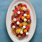 A large white platter filled with halved various colored cherry tomatoes, labneh balls, olive oil, and a sprinkle of spices.