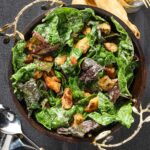 A dark bowl with handles full of Swiss chard Caeser salad and croutons on a dark background.