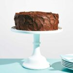 A yellow cake with chocolate frosting on a cake stand with a stack of plates beside it.
