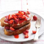 A white plate with 2 pieces of challah French toast covered with fresh strawberries, icing sugar and being drizzled with strawberry syrup.