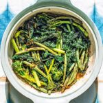 A soft green casserole dish filed with lightly charred broccolini, kale, and green beans, sprinkled with chile flakes and garlic.