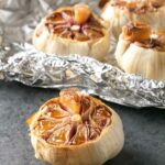 4 bulbs of roasted garlic with the tops cut off, 3 lying on a sheet of aluminium foil.