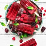 White barn board with a green bowl filled with ice and frozen berries, and 5 deep red raspberry hard seltzer popsicles lying on top, garnished with fresh mint leaves.