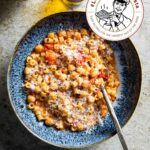 A blue bowl filled with chickpeas, diced tomatoes, ditalini pasta, and parmesan, flanked with a crueset of olive oil and a bowl of Parmesan.