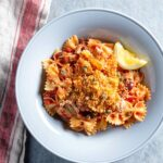 A pale blue bowl filled with farfalle, tuna, capers, tomatoes, and topped with bread crumbs and a slice of lemon, sitting on a red and white dish cloth.