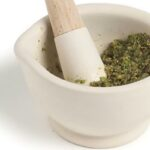 A mortar filled with ingredients for a Thai peppercorn-cilantro root paste--garlic, black peppercorns, cilantro stems