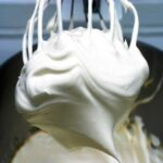 A large stand-mixer beater covered with white, fluffy seven minute frosting.