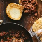 A skillet filled with sloppy Joe meat mixture, flanked by a filled, untapped sandwich with a toasted top and a bag of sesame seed buns.