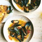 2 white plates with mussels in sauce, with tomatoes, chorizo, and parsley. A piece of buttery toasted bread to the side.