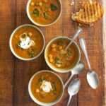 . Each bowl is filled with tomato soup with chickpeas and spinach and topped with yogurt.