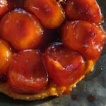 An apple tart Tatin with a shortcrust pastry bottom, sitting on a piece of parchment paper with drips of caramel.